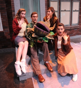 "Seymour (Preston Pounds) and Audrey II are surrounded by ""Urchins"" Monica Brown, Marina Pires and Haley Jones (from left) in Little Shop of Horrors (photo by Ed Syguda)"